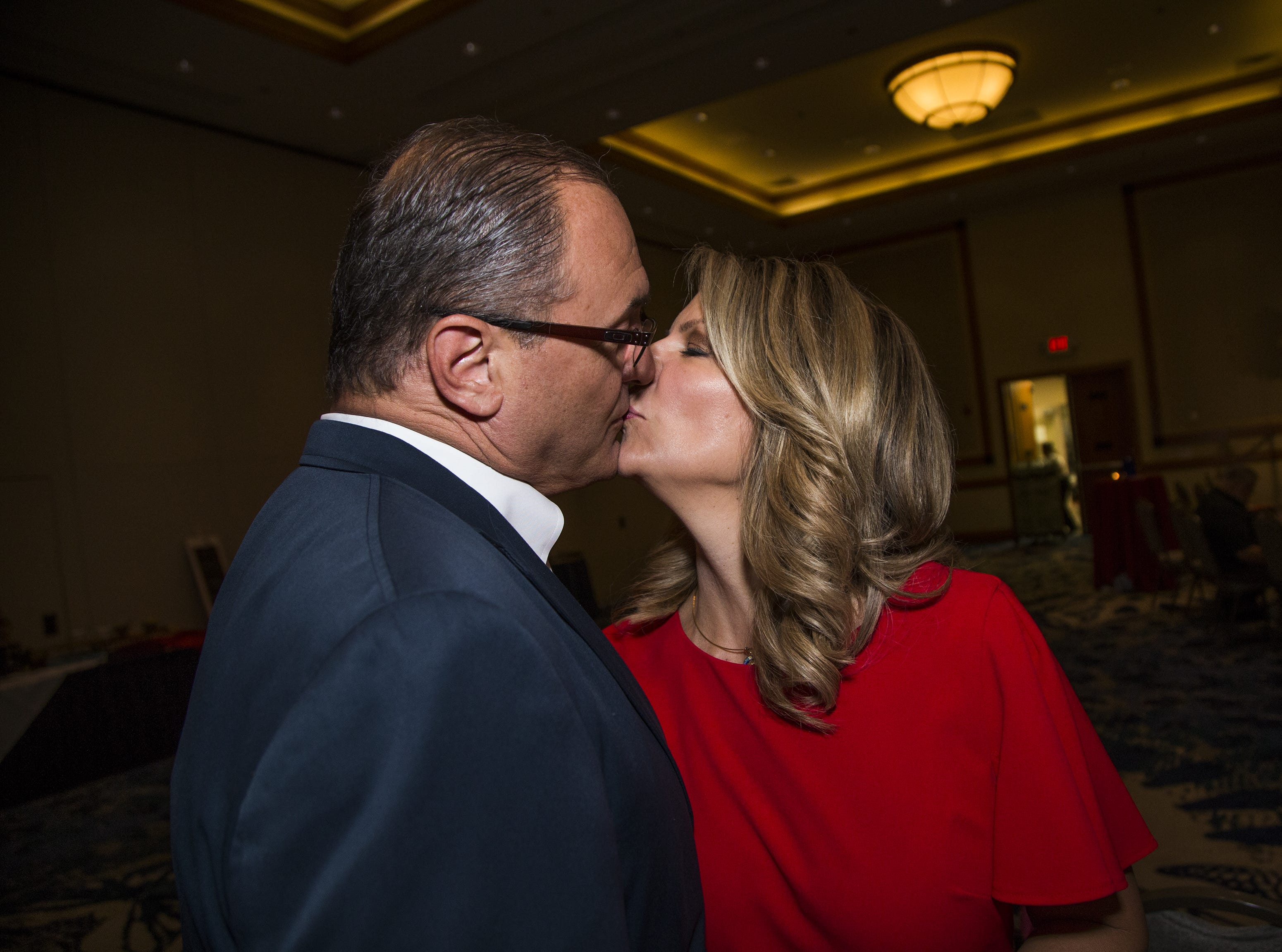 Kelli Ward gets a kiss from her husband, Dr. Michael Ward, before greeting a primary election night party at Embassy Suites Scottsdale on Aug. 28, 2018.