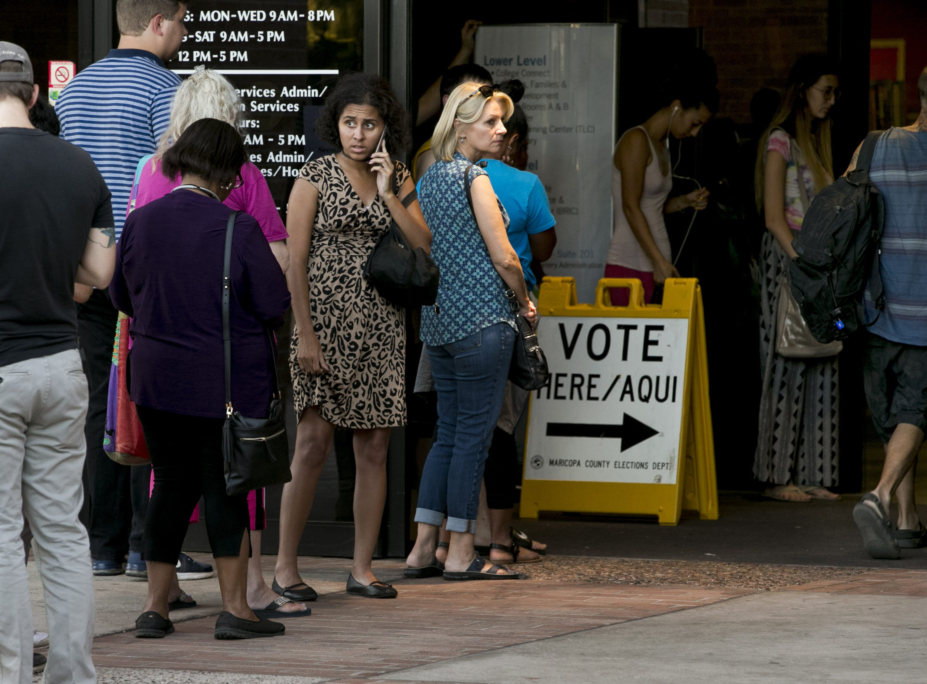 People wait in line to vote at the Tempe Public Library polling place on Aug. 28, 2018. People leaving the polling place said they waited in line for an hour.
