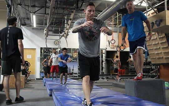 Brian Rambo, 38, who has competed on the TV show, and other members warm up with exercises focusing on flexibility, grip strength and tumbling.