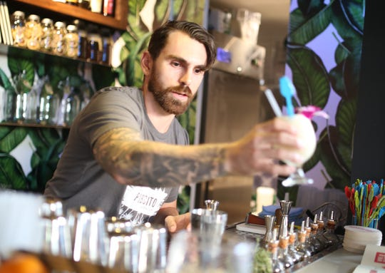 A bartender prepares a cocktail at Pobrecito at the Churchill in downtown Phoenix.