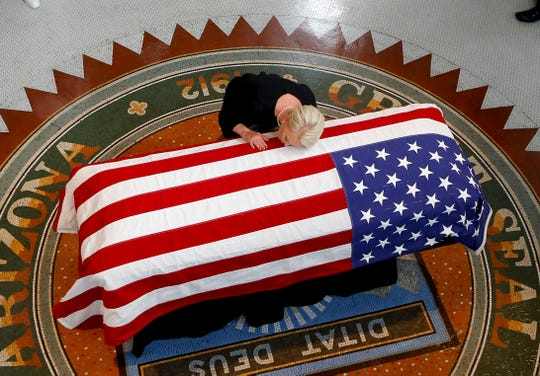 Cindy McCain, wife of Sen. John McCain, R-Ariz., lays her head on his casket during a memorial service at the Arizona Capitol on Aug. 29, 2018, in Phoenix.
