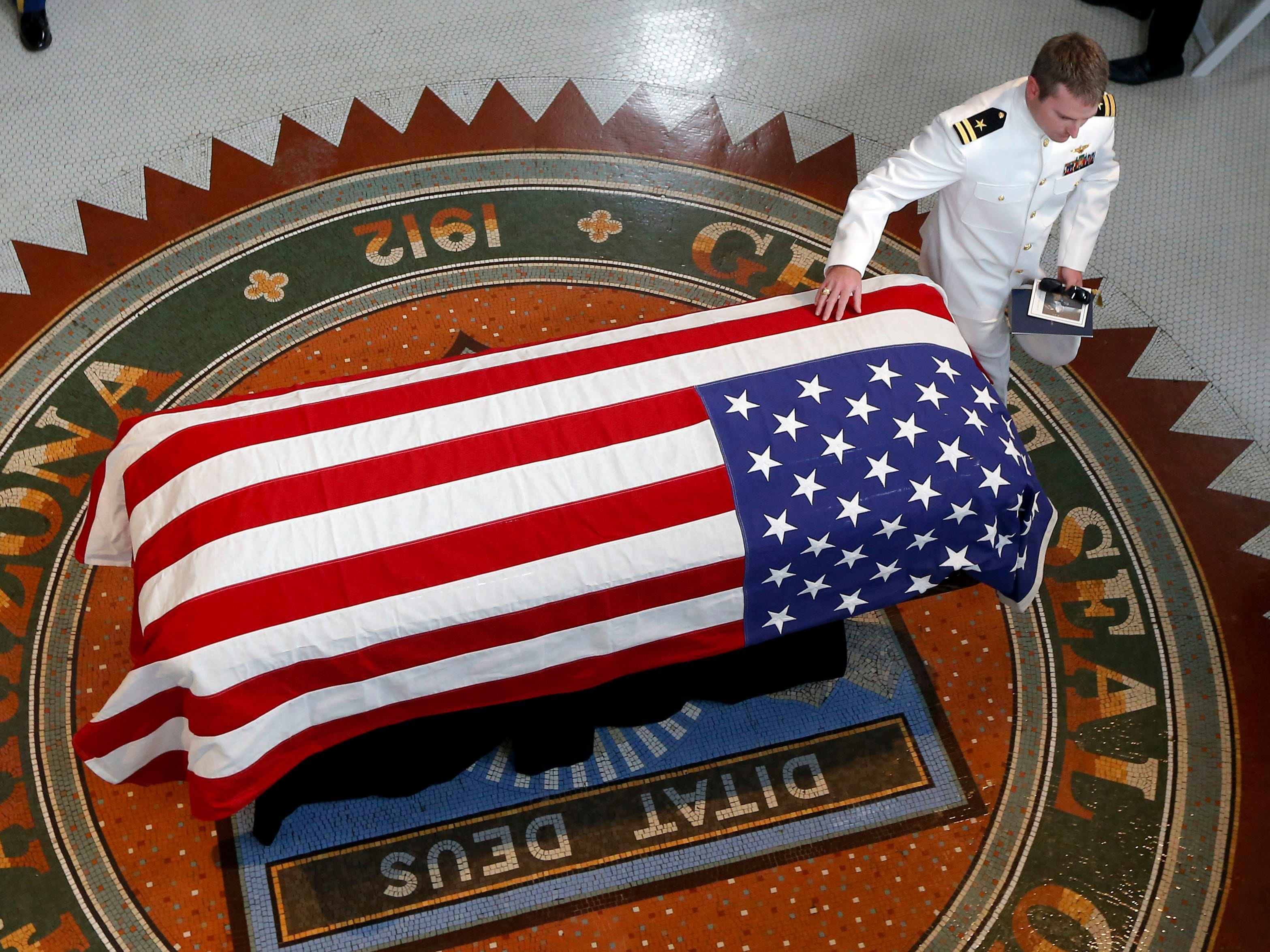 Jack McCain, son of Sen. John McCain, R-Ariz., touches the casket during a memorial service at the Arizona Capitol on Aug. 29, 2018, in Phoenix.