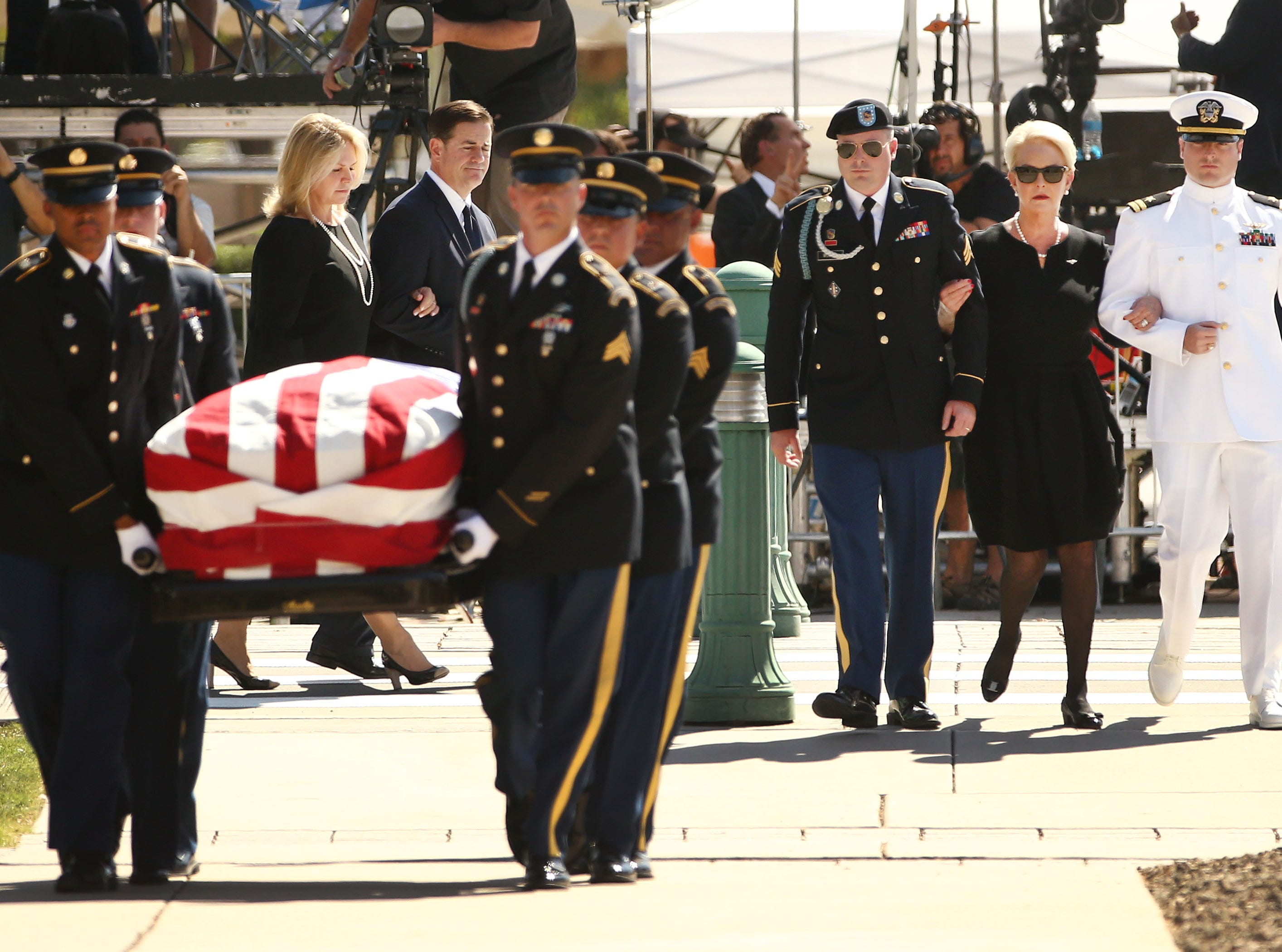 Mrs. Cindy McCain is escorted by her sons, Jimmy McCain and Jack McCain, and Arizona Gov. Doug Ducey and First Lady Angela Ducey (left) as they follow the casket of U.S. Sen. John McCain for his memorial service at the Arizona State Capitol on Aug. 29, 2018, in Phoenix, Ariz.