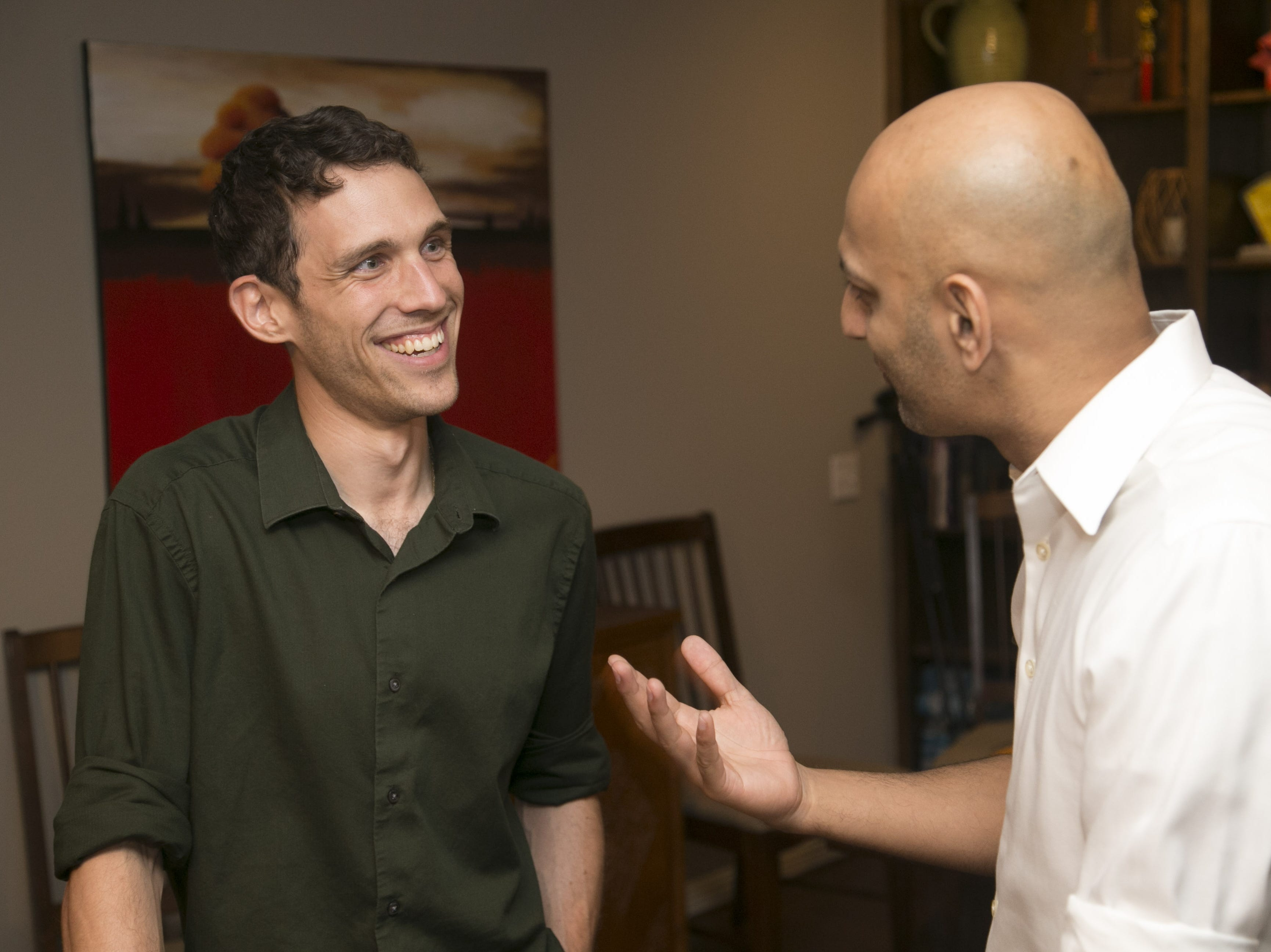 Jonathan Gelbart, (left) a Republican primary candidate for state superintendent of public instruction, speaks with supporter Ronjon Bhattacharya at a watch party at his Tempe home on Aug. 28, 2018.