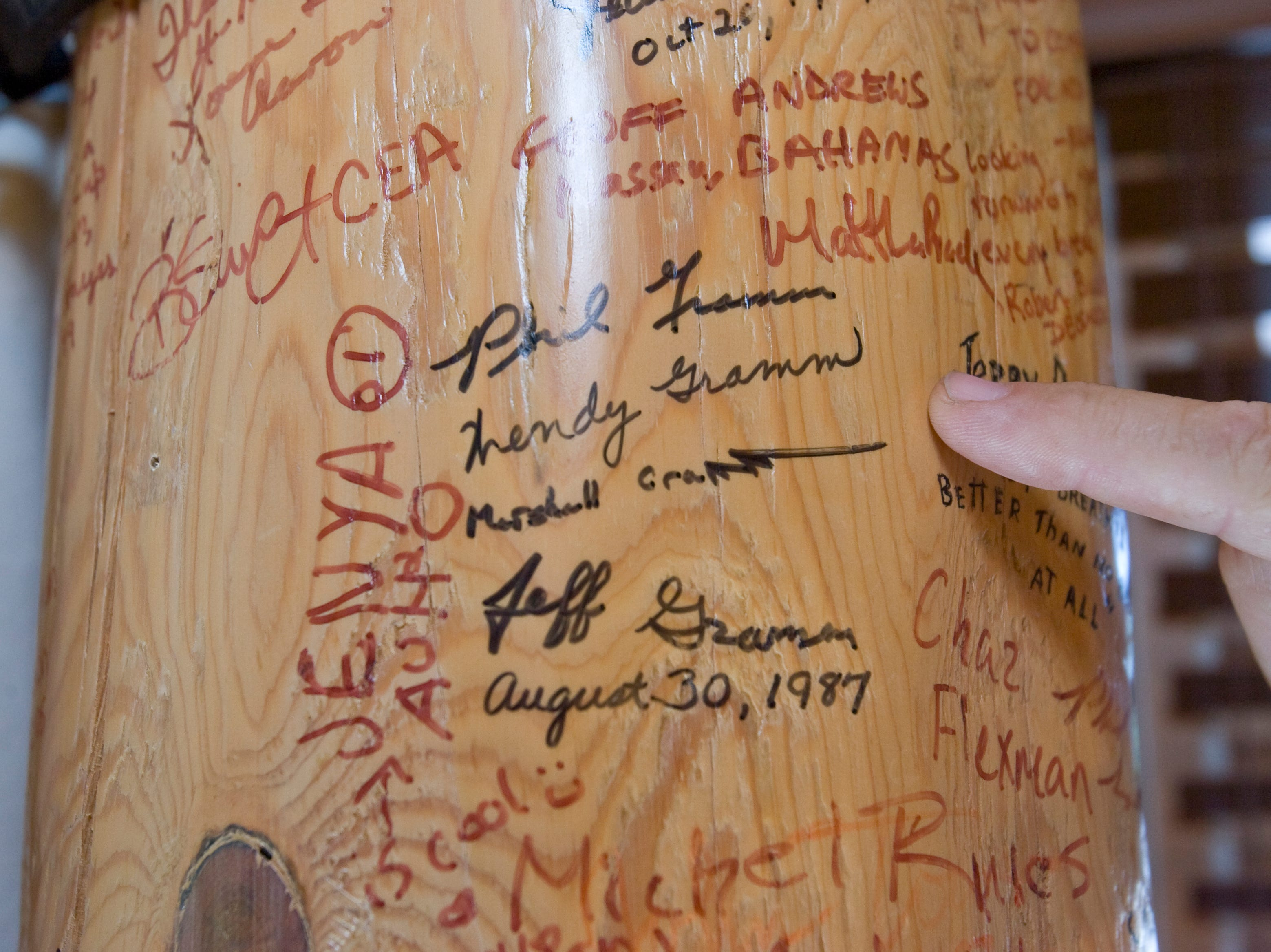 Auctioneer Stewart Larsen points to a wooden pole in the swimming pool changing room at the former home of  Sen. John and Cindy McCain in 2008. Guests who visited the home signed their names and often left quotes and comments.