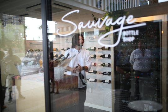 Patrons peer through the windows at wine bottles and staff inside Sauvage Bottle Shop at the Churchill in downtown Phoenix.