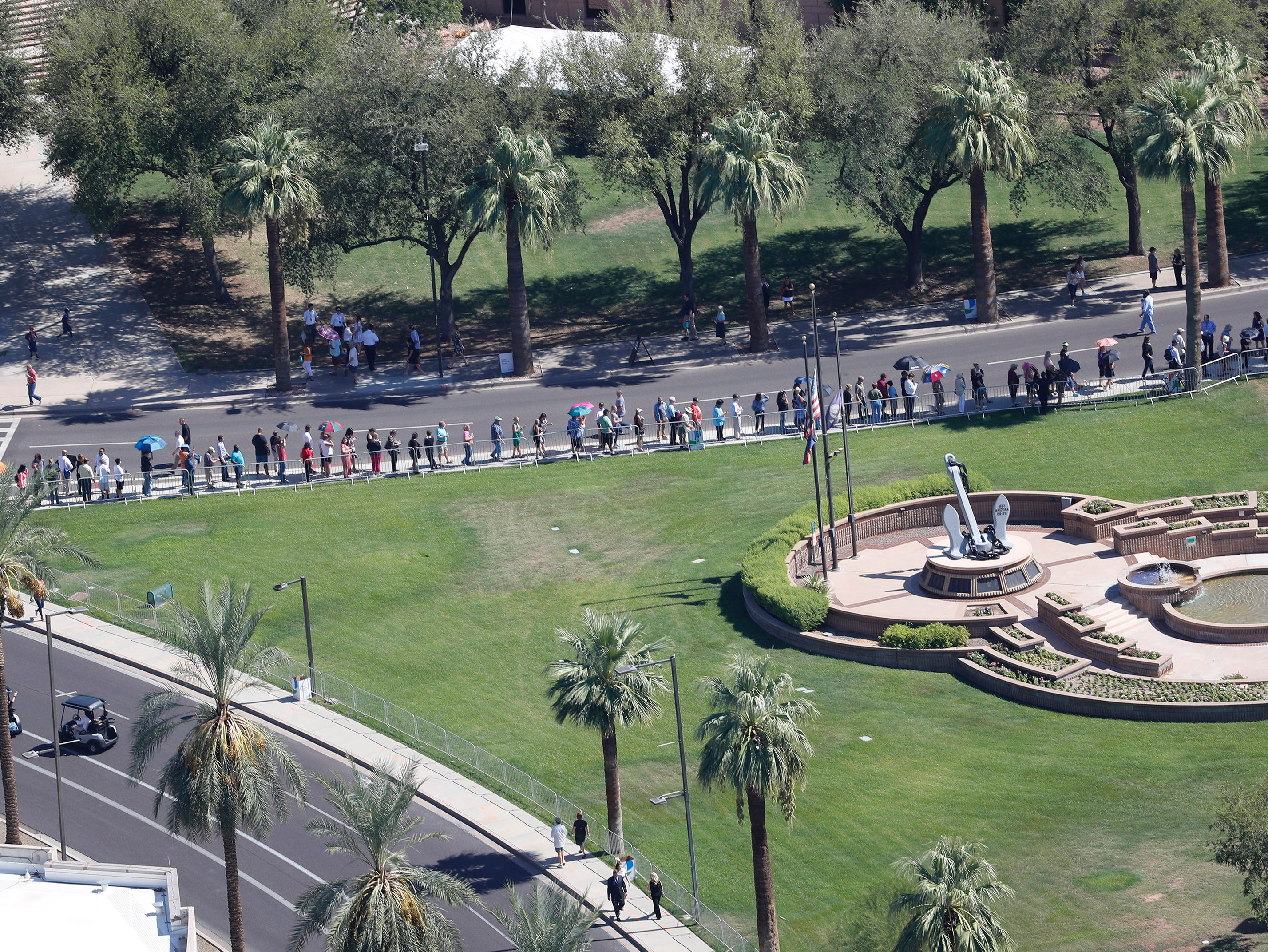 People line up outside the Arizona state Capitol, where Sen. John McCain lies in state in Phoenix Aug. 29, 2018. The six-term Arizona senator died Saturday after a 13-month battle with brain cancer..