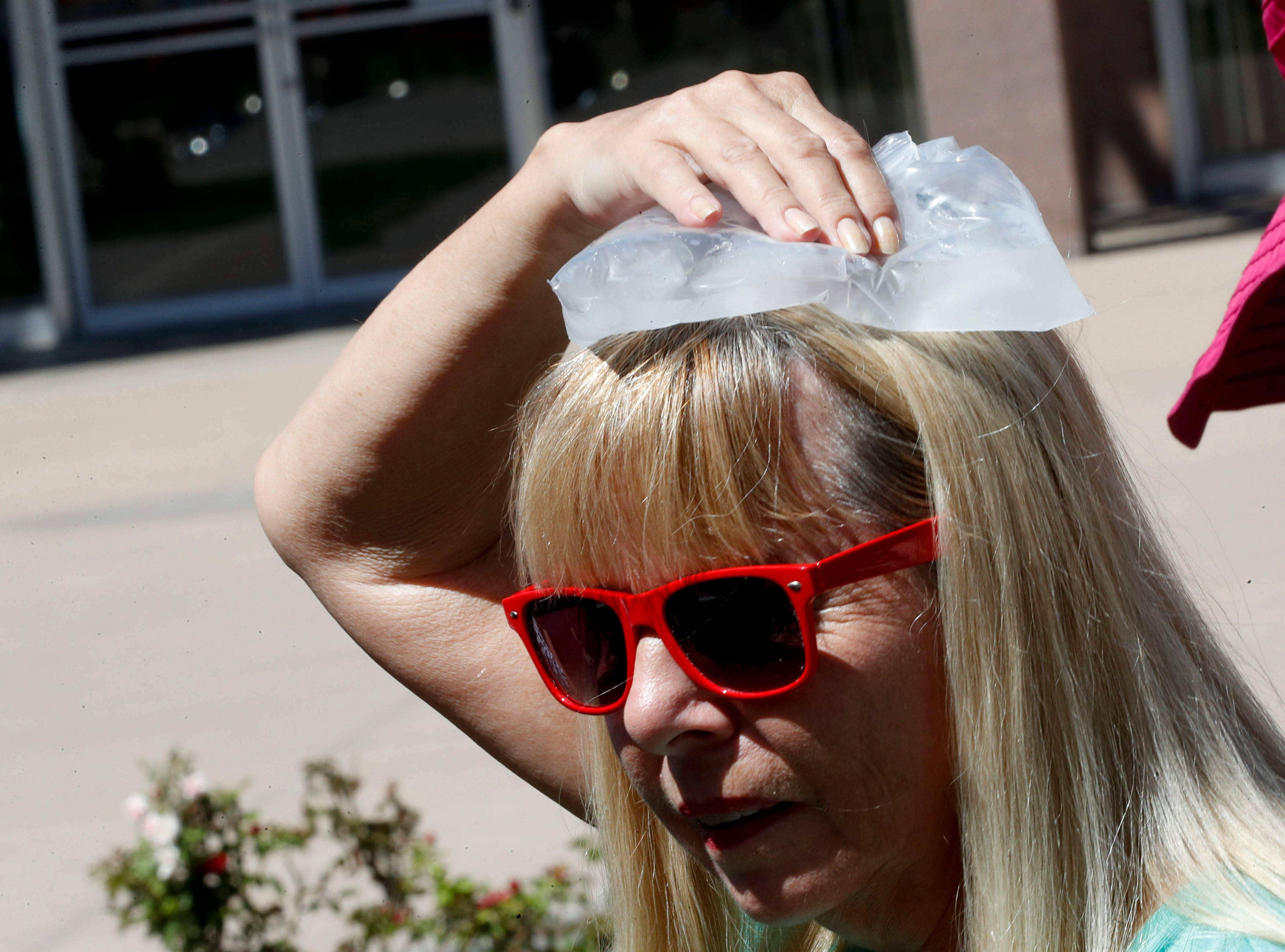 A woman cools off with an ice pack waiting in line to play respects to Sen. John McCain during a viewing at the Arizona Capitol on Aug. 29, 2018, in Phoenix.