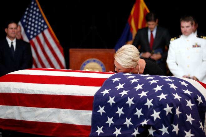 Cindy McCain, wife of Sen. John McCain, R-Ariz., touches the casket during his memorial service at the Arizona Capitol on Aug. 29, 2018, in Phoenix.
