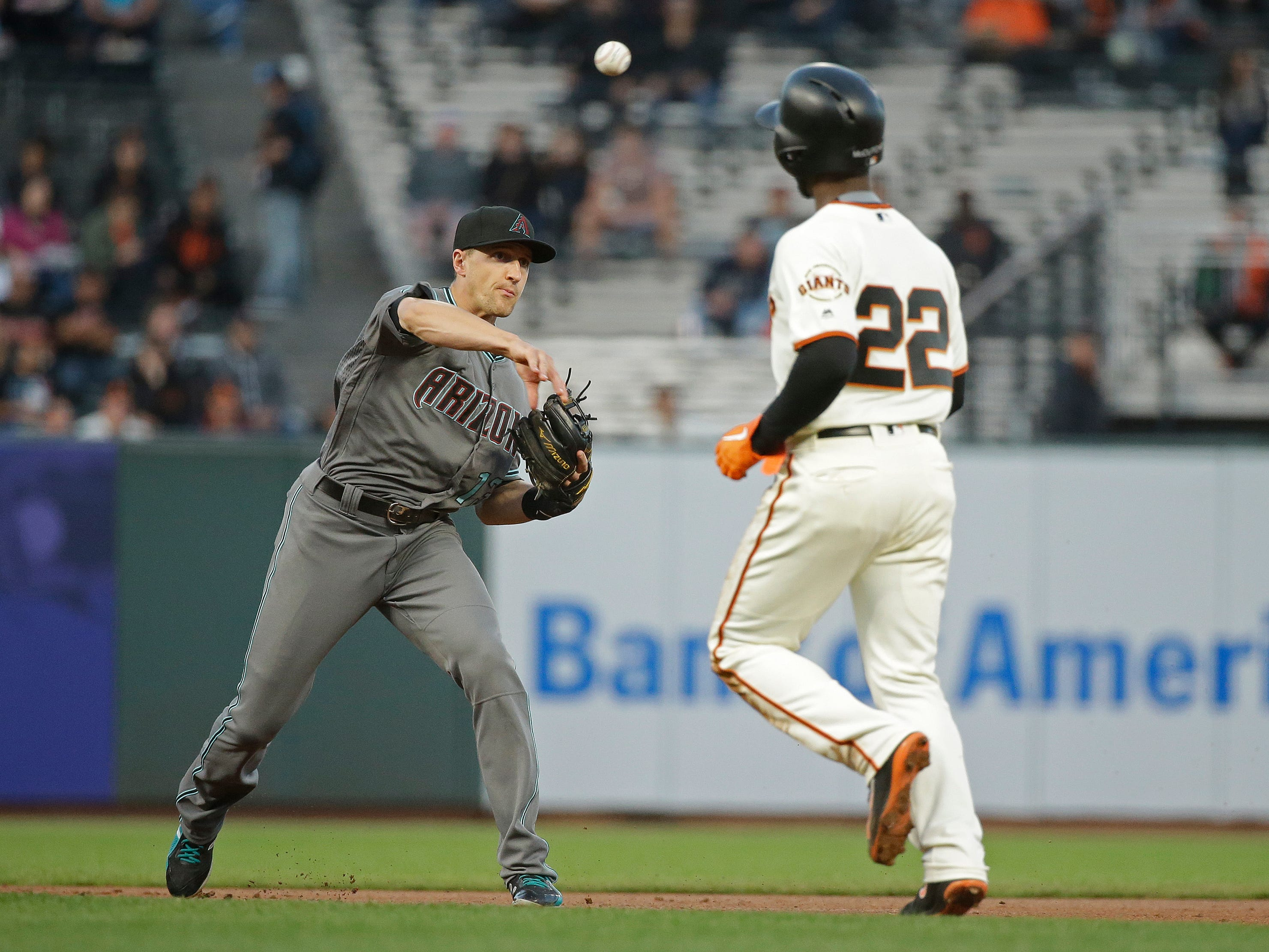 Arizona Diamondbacks shortstop Nick Ahmed turns a double play as San Francisco Giants' Andrew McCutchen runs to second base in the first inning of a baseball game Tuesday, Aug. 28, 2018, in San Francisco.