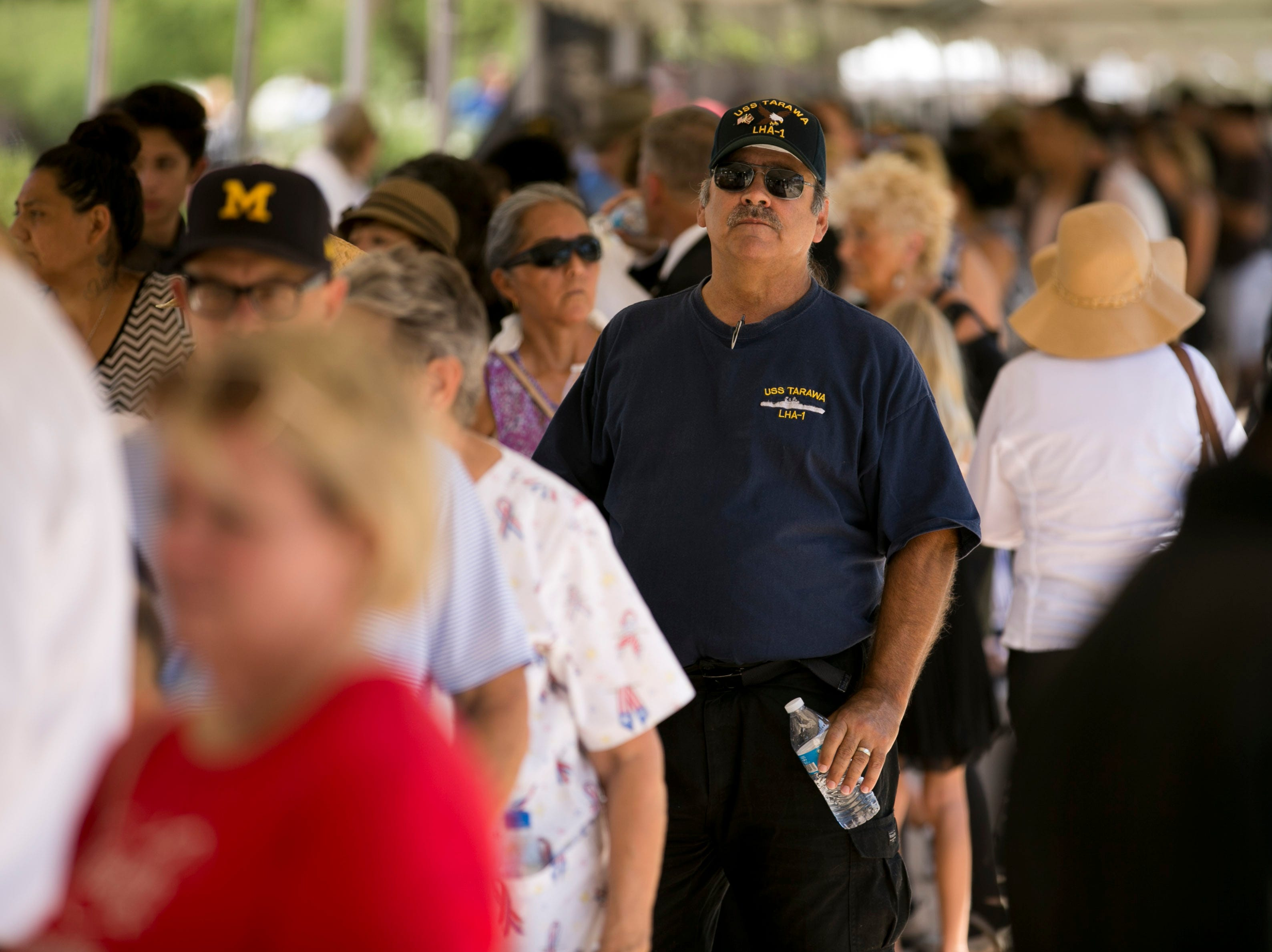Larry Osborn, (center) of Phoenix and a veteran of the U.S. Navy, people wait in line to enter the Arizona state capitol during a public viewing as Senator John McCain lies in state in the state capitol in Phoenix on Wednesday, August 29, 2018.