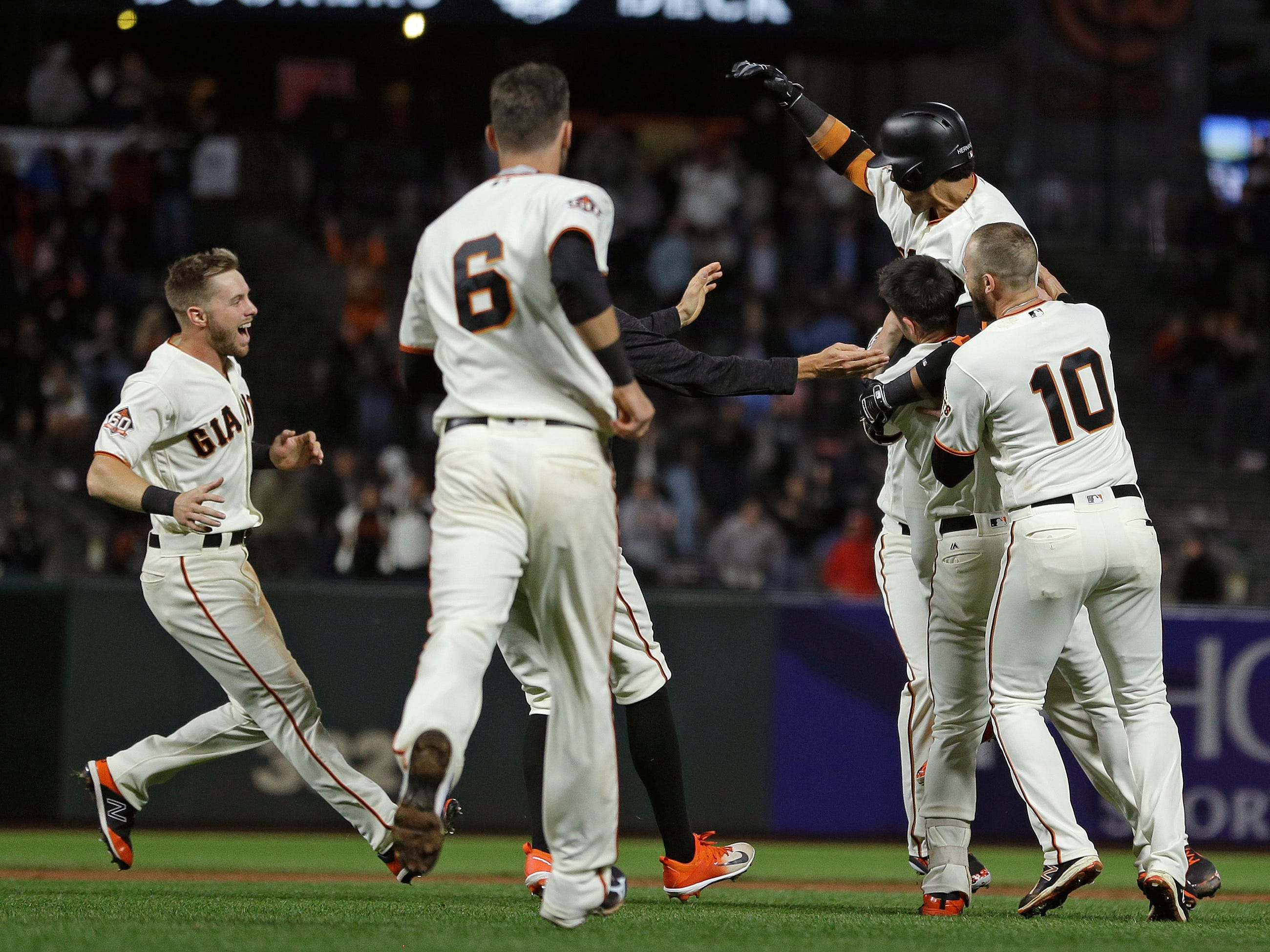 San Francisco Giants' Gorkys Hernandez, top right, is mobbed by his teammates after hitting a walk-off single against Arizona Diamondbacks relief pitcher Jake Diekman in the ninth inning of a baseball game, Tuesday, Aug. 28, 2018, in San Francisco. San Francisco won the game 1-0. (AP Photo/Eric Risberg)