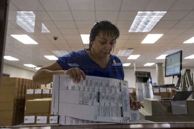 A Maricopa County Recorder and Elections Department worker tabulates ballots on Aug. 28, 2018, at the Maricopa County Recorder's office in Phoenix.