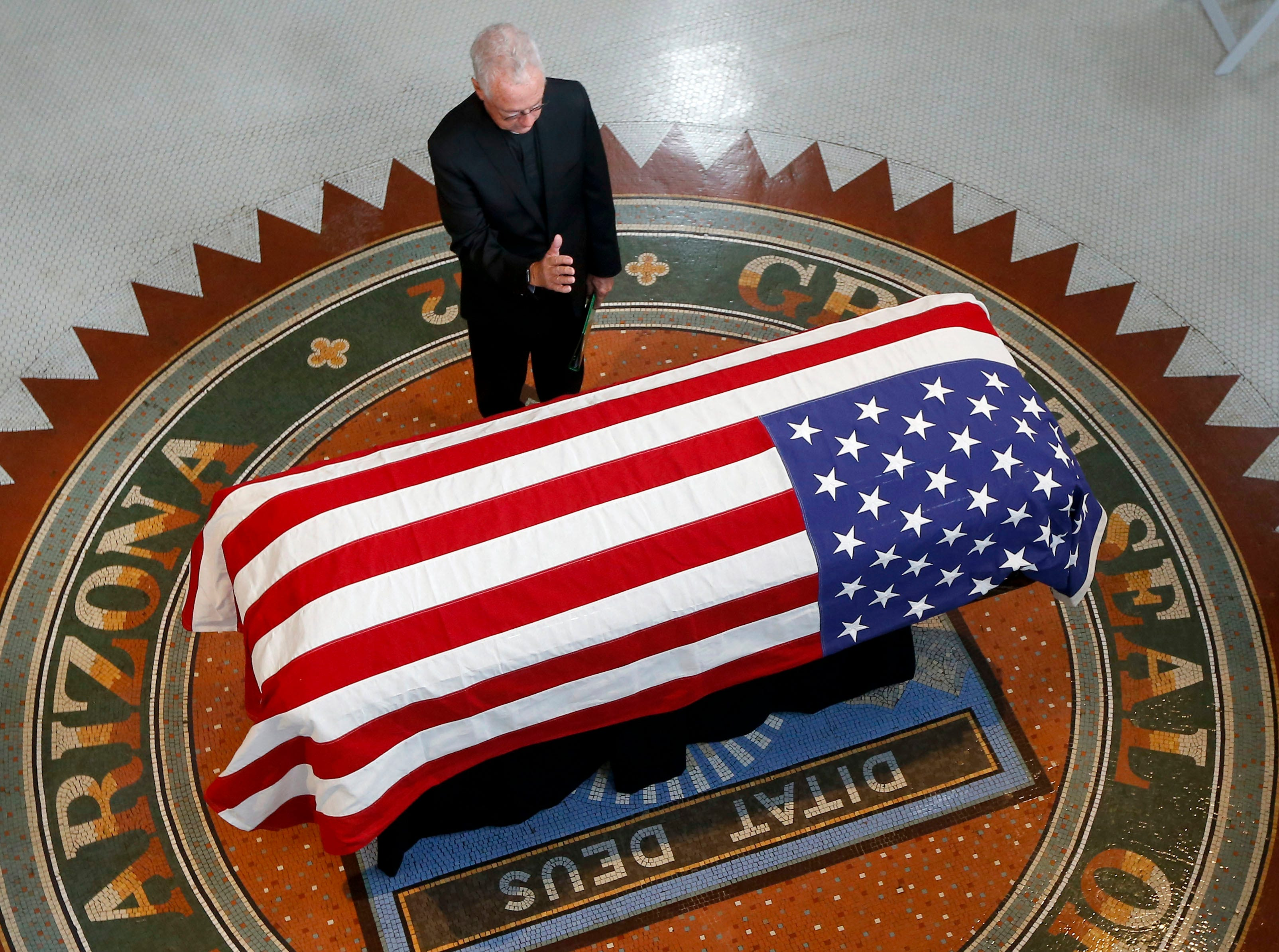 Father Edward A. Reese prays over the casket during a memorial service for Sen. John McCain, R-Ariz., at the Arizona Capitol on Aug. 29, 2018, in Phoenix.