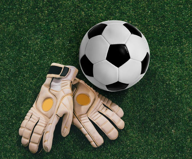 Getty Images/iStockphoto Soccer ball and goalkeeper gloves on the grass
