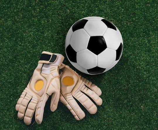 Soccer ball and goalkeeper gloves on the grass