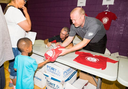 Port Huron Schools Superntendent Jamie Cain, right, hands a package of school uniforms to second-grader Da'jon Dix, 5, Tuesday, Aug. 28, 2018, during an open house at Literacy Academy of Cleveland.