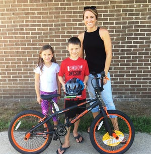 Brayden Kirkpatrick, with his mother, Tonya, and his sister, Keira, won a boys' bike in the Sanilac County DARE drawing at the county fair.