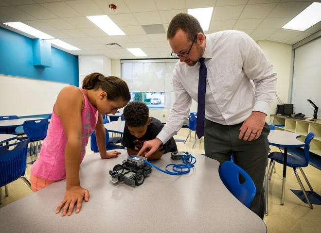STEAM Coach Craig Archer, right, talks to Mconilly Price, 10, and his sister Paige, 12, about one of the VEX robots students will build this year Tuesday, Aug. 28, 2018, during an open house at the STEAM Academy at Woodrow Wilson. Some of the students attending the school will learn how to build robots that can move objects.