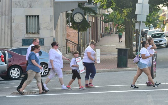 Walkers cross the street during a Recovery Walk along East Main Street. Esther House held a Recovery Awareness Walk in Waynesboro, Tuesday, August 28, 2018 as a group of supporters and other family walked along Main Street, Waynesboro.