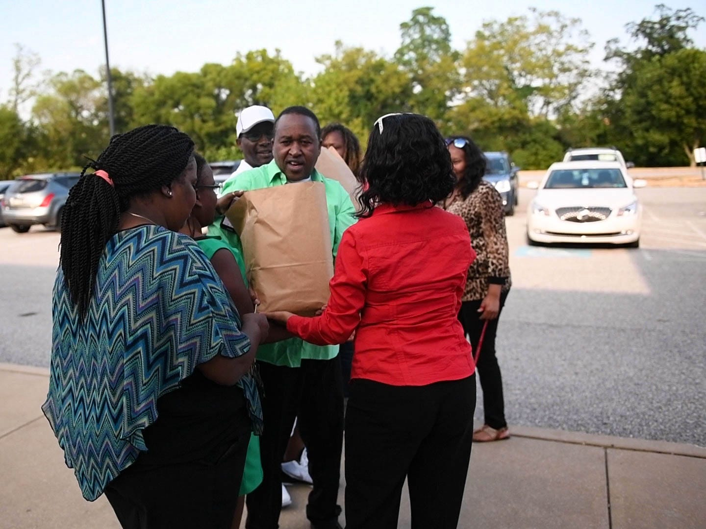 Gichuhi's family help carry two brown bags filled with Sammy's personal effects to the car.