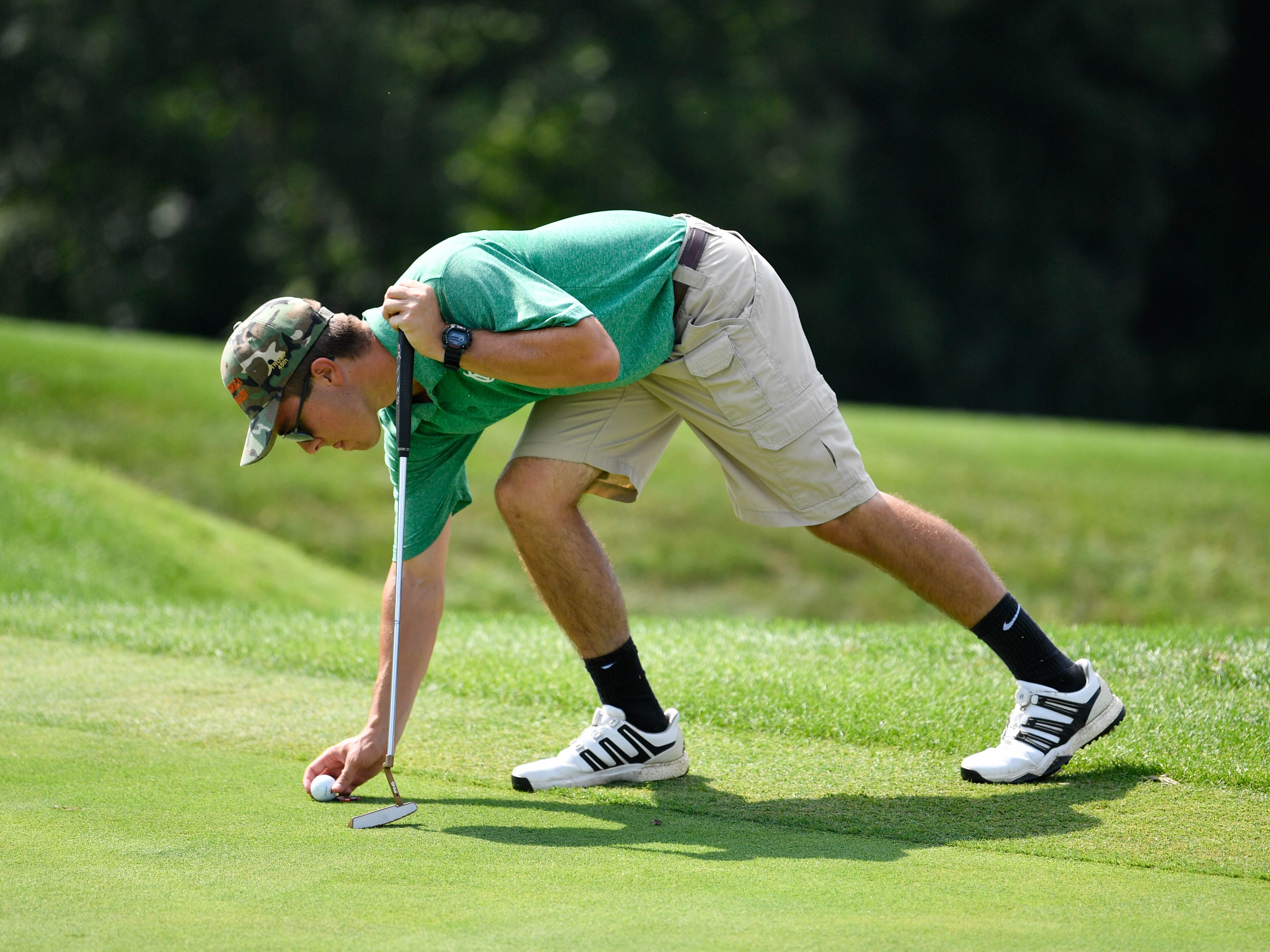 Ben Andrasi of York Catholic High School sets up for the putt during a division III golf match at Regents Glen Country Club on August 28.