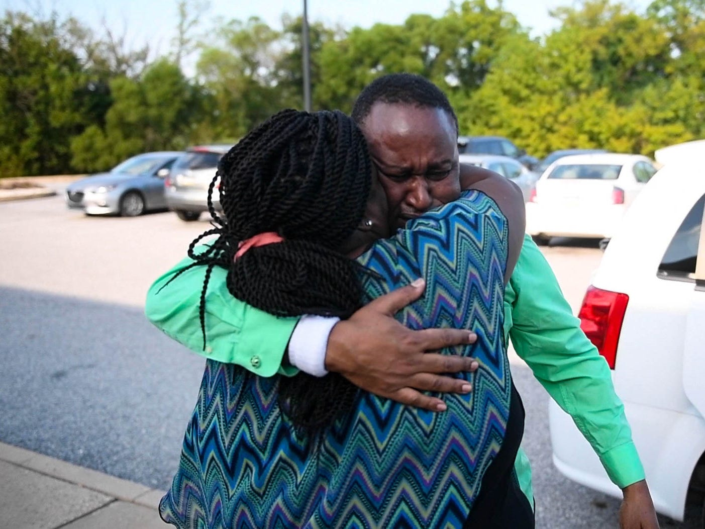 Grace Kuria is the first to get to Gichuhi, throwing her arms around him with tears in her eyes.