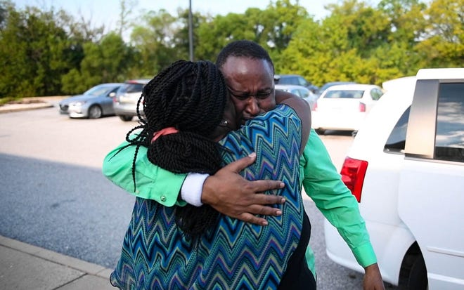 Grace Kuria is the first to get to Sammy Gichuhi upon his release on bail from York County Prison, throwing her arms around him with tears in her eyes.
