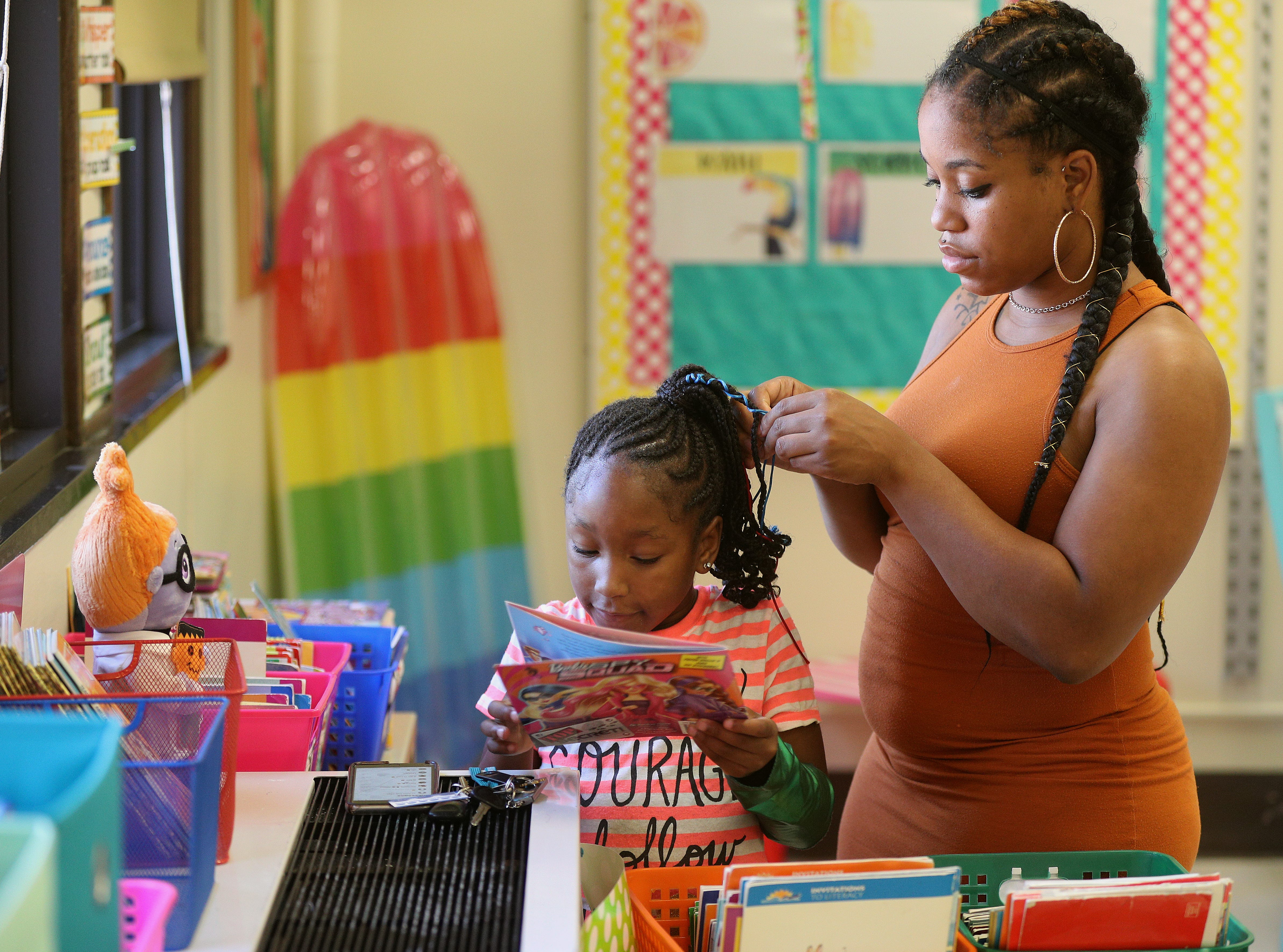 Kanyia William reads a book while her mother Keisha Kennedy braids her hair.  They were able to visit classrooms in RISE Community School where Kanyia will be in first grade.