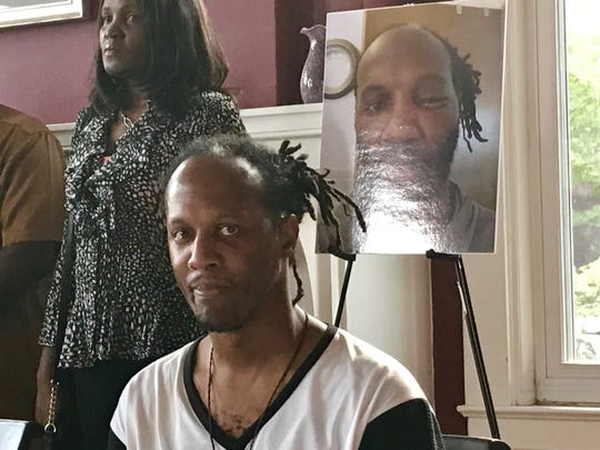 Christopher Pate sits in front of a photo that shows the injuries he suffered in alleged police assault May 5.