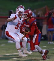 Fairport quarterback Mike Pellittiere eludes a Penfield defender during a game last season.