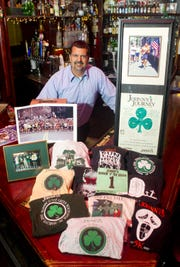 John Savino, owner of Johnny's Irish Pub, is surrounded by Johnny's Runnin' O the Green 5-mile race memorabilia. This marks the 15th year he has sponsored the event.