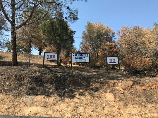 """On the """"yes"""" side, the trees are trimmed and the proper distance away from one another. On the """"no"""" side, firefighters showed the raw wildlife that some people have closing in on the eaves of their home. The sign display is outside Cal Fire Station No. 58 on Tuesday, Aug. 18, 2018."""