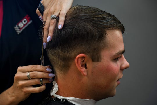 Stylist Molly Shackelfort gives Shorebirds player Will Robertson a haircut at Sport Clips Haircuts on Monday, Aug. 20.