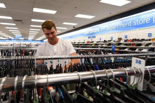 Shorebirds player Will Robertson browses through shirts at Ross before the game on Monday, Aug. 20. He said minor league baseball players have to find bargains to make it by on their limited salary.
