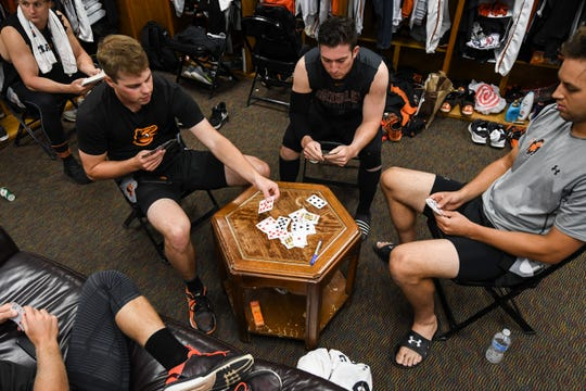 Shorebirds player Will Robertson plays cards with catcher Ben Breazeale and first baseman Ryan Ripken before a game on Monday, Aug. 20.