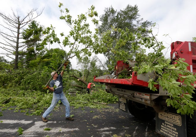 Willie Trakel of Plymouth, Wis., tosses a branch into a dump truck during post-storm cleanup operations, Wednesday, August 29, 2018, in Cascade, Wis.