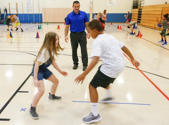 Levi Neville watches as students run a football drill during his physical education class at Wilson's Creek Intermediate School on Wednesday, Aug. 29, 2018.