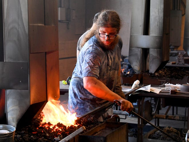 Jon Mintor of Maryland sticks the iron back in the fire of the forge. He works on a project at the Virginia Institute of Blacksmithing in Waynesboro on Friday, August 24, 2018. Mintor is close to becoming a certified apprentice artistic blacksmith.