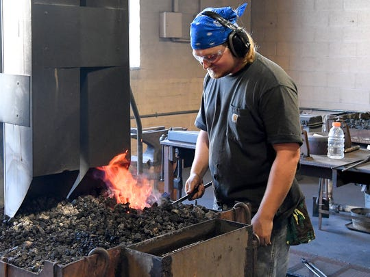 Perrin Gunderson of Luray stokes up the flames of the forge as he works on a project at the Virginia Institute of Blacksmithing in Waynesboro on Friday, August 24, 2018. Gunderson is close to becoming a certified apprentice artistic blacksmith.