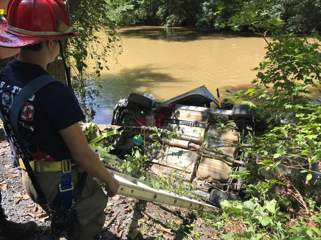 A firefighter watches as another checks the vehicle identification number of a car found submerged in the Middle River on Wednesday.