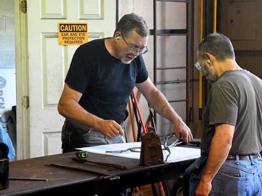 Dale Morse, blacksmithing instructor and co-founder of the Virginia Institute of Blacksmithing, compares the iron's shape so far against the plans for it as he assists student Jim Miele of New Jersey with his project at the institute's workshop in Waynesboro on Friday, August 24, 2018.
