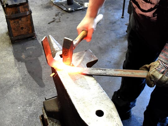 Keith Zimmerman of Staunton pounds the hot metal slowly into the shape he wants while working on a project at the Virginia Institute of Blacksmithing in Waynesboro on Friday, August 24, 2018.  Zimmerman is close to becoming a certified apprentice artistic blacksmith.