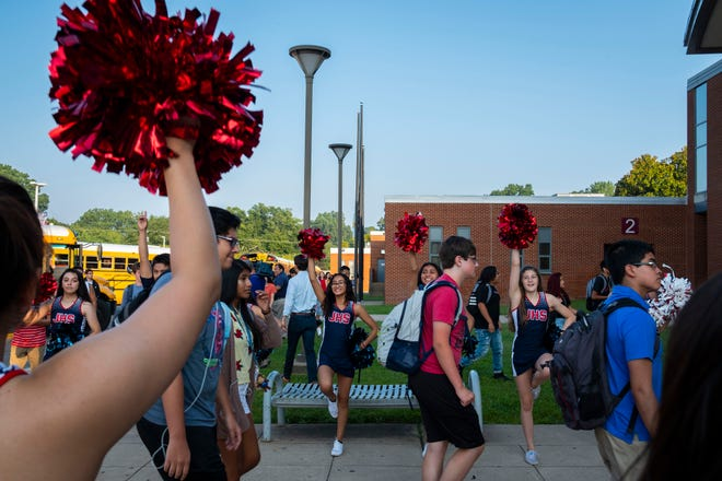 Cheerleaders welcome students as they get off their buses on the first day of school at the newly named Justice High School in Falls Church, Va.