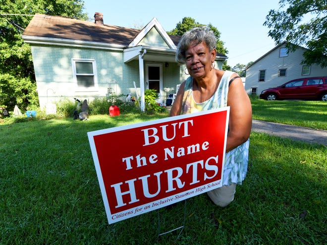"Sharon Wells kneels next to the ""But The Name Hurts"" sign in her front yard in Staunton on Wednesday, August 29, 2018. Wells has lived in Staunton all her life and graduate from Robert E. Lee High School in 1971."