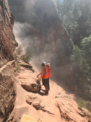 Representatives from the U.S. Geological Survey survey the scene of a rockfall on the Hidden Canyon Trail inside Zion National Park on Aug. 28.