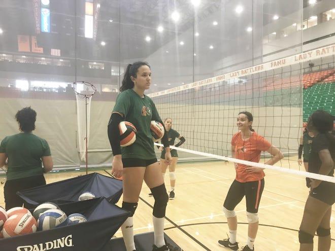 Nair Mendoza looks over as teammates work on digs in practice.