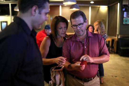 Leon County School Board member Alva Striplin checks her husband George Smith's phone as results come in for her potential re-election during her watch party at Fifth and Thomas on Tuesday, Aug. 28, 2018.