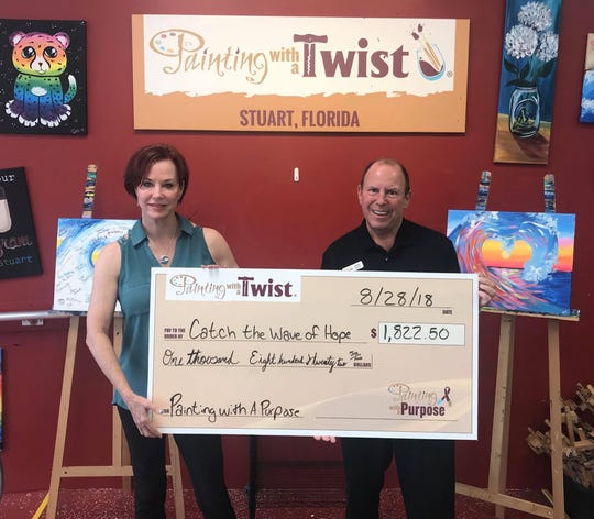 Mark Sandler, right, owner of Painting with a Twist, presents Lynne Barletta with a check for $1,822.50 from the Aug. 23 Painting with a Purpose fundraiser for Catch the Wave of Hope.