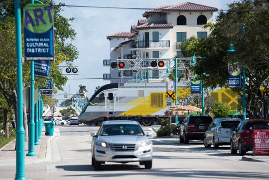 A Brightline train traveling north crosses East Ocean Avenue and Northeast Fourth Street in Boynton Beach.
